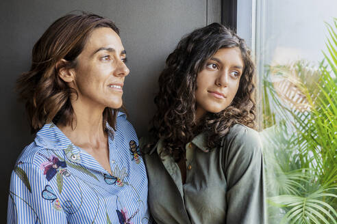 Mother and daughter looking through window while standing at home - DLTSF01311