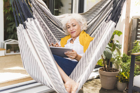 Mature woman using digital tablet while sitting on hammock at home - UUF21626