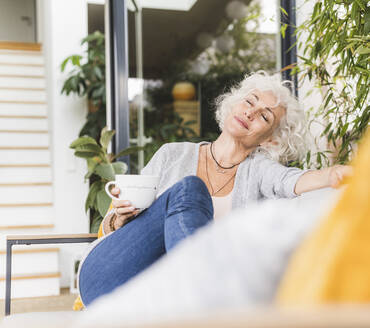 Mature woman with eyes closed with coffee cup sitting on couch at home - UUF21653