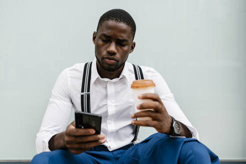 Young businessman using smart phone while holding reusable cup and sitting against window in city - EGAF00811