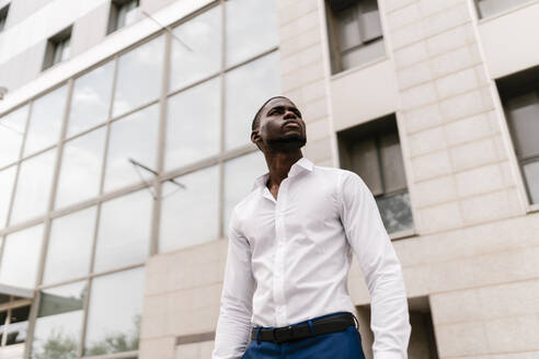 Confident businessman looking away while standing against office building in city - EGAF00835