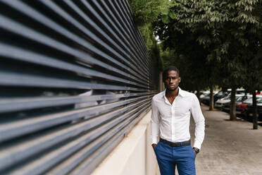 Confident African professional standing with hands in pockets by surrounding wall in city - EGAF00838