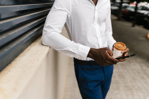 Young male professional holding reusable cup and using smart phone while leaning on surrounding wall - EGAF00841