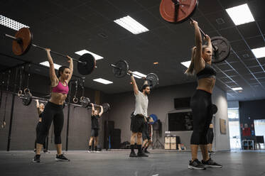 Athletes lifting barbell while exercising in gym - SNF00553