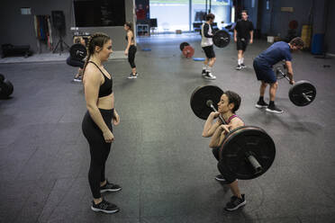 Athlete helping each other while exercising in gym - SNF00556