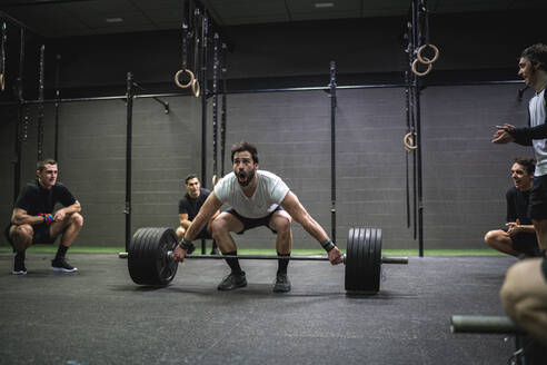Athlete cheering man crouching while lifting barbell at gym - SNF00559