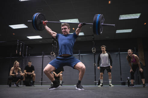 Athletes cheering man picking barbell while standing at gym - SNF00562
