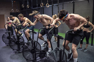 Athletes cycling on exercise bike with women standing in background at gym - SNF00571