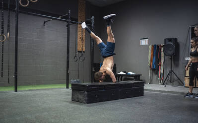 Adaptive athlete doing handstand while exercising at gym - SNF00577