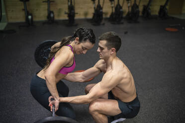 Man helping woman while picking up barbell at gym - SNF00589