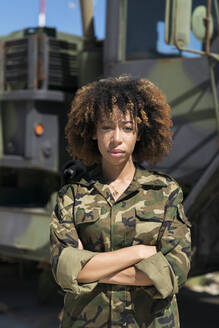 Confident young female army soldier with arms crossed standing against truck at military base - MTBF00669