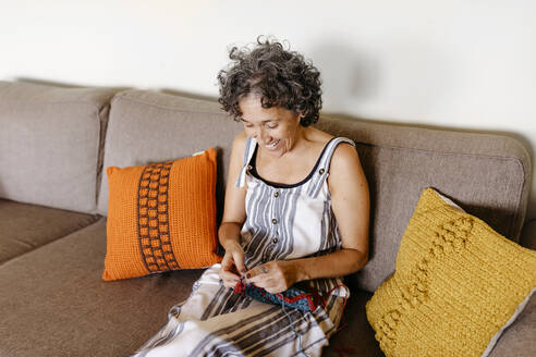 Smiling woman knitting while sitting on sofa at home - TCEF01192