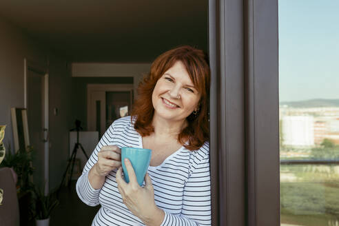 Smiling woman drinking coffee while standing by window at home - VABF03562