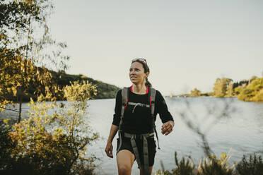 Woman walking against river by Sierra Morena mountain at Sierra De Hornachuelos, Cordoba, Spain - DMGF00154