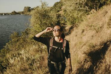 Smiling woman trekking on footpath at Sierra De Hornachuelos, Cordoba, Spain - DMGF00160