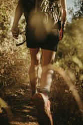 Trekker with backpack walking on narrow path at Sierra De Hornachuelos, Cordoba, Spain - DMGF00175