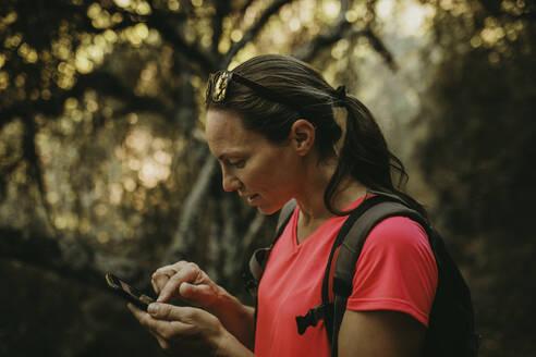 Trekker using mobile phone while standing at Sierra De Hornachuelos, Cordoba, Spain - DMGF00178