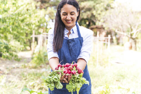 Happy woman showing freshly harvested organic radishes from garden - FMOF01188