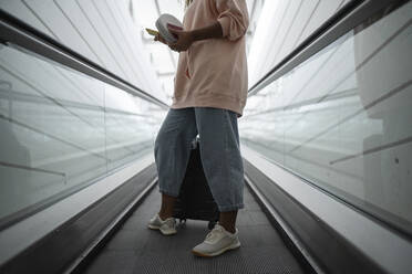 Legs of woman standing on escalator at airport - SNF00596