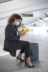 Young woman wearing face mask reading book while sitting at airport - SNF00599