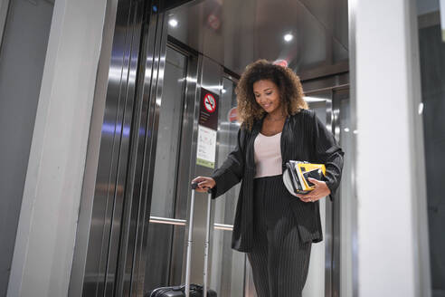 Young woman looking down while standing in elevator at airport - SNF00602