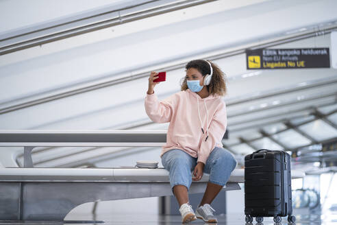 Young woman taking selfie while listening music through headphone at airport - SNF00611