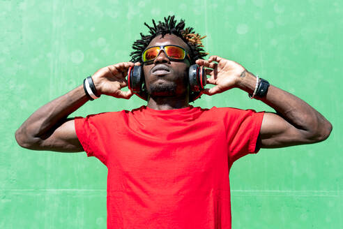 African American male athlete in sportswear and with headphones relaxing on street after training on sunny day while looking away - ADSF16183