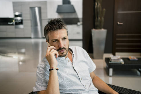Handsome businessman talking on smart phone while working at office - RCPF00304