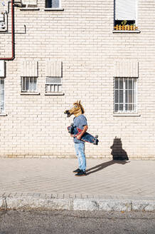 Man wearing horse mask holding skateboard on footpath by building in city during sunny day - JCMF01537
