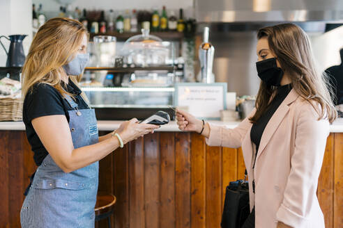 Businesswoman in face mask paying through credit card in cafe during coronavirus crisis - EGAF00897