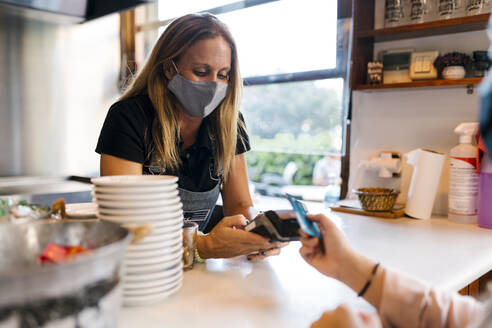Female cashier in face mask receiving payment through credit card in cafe during COVID-19 - EGAF00900