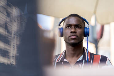Confident young man looking away while listening music through headphones at cafe - EGAF00915