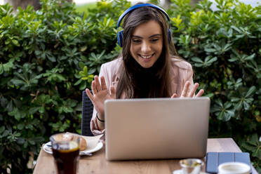 Smiling female entrepreneur video calling through laptop while sitting on terrace at cafe - EGAF00918