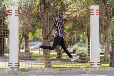 Cheerful young man jumping against fence at park - EGAF00927