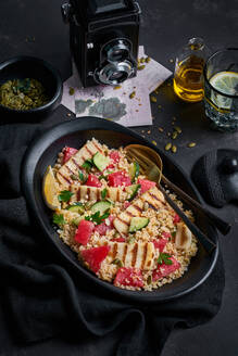 High angle of delicious Bulgur salad with Halloumi cheese and ripe ingredients placed on table with lemon water and pumpkin seeds for lunch - ADSF16528