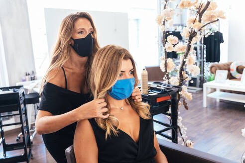 Hairstylist in protective mask adjusting hairdo of female client in salon while working during coronavirus and reflecting in mirror - ADSF16552