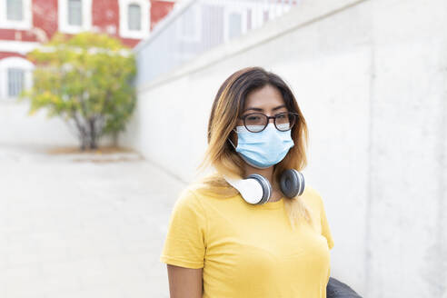 Young woman wearing protective mask and eyeglasses at bus stop - JPTF00589