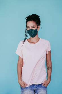 Caucasian woman wearing protective face mask looking away while standing with hands in pockets against turquoise background - EBBF00795