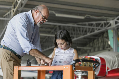 Grandchild and grandfather selecting tools to fix aircraft - EIF00192