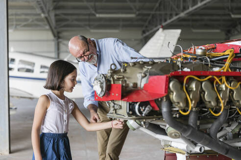 Grandfather showing how to fix airplane tool to granddaughter while standing in hangar - EIF00195