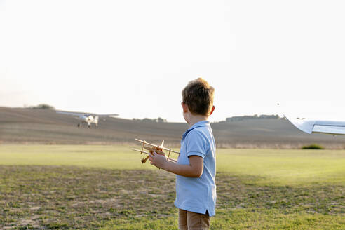 Little boy holding toy airplane while standing at airfield - EIF00225