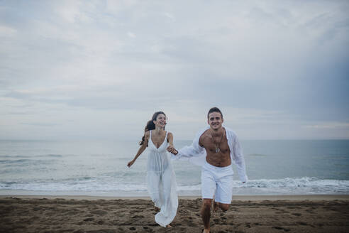 Happy couple holding hands while running on beach - GMLF00673