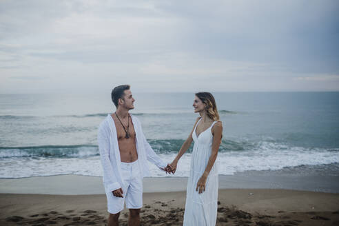 Young couple looking at each other while standing on beach - GMLF00676