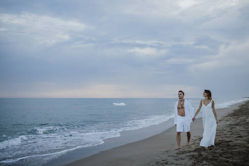 Young couple holding hand while walking on beach during sunset - GMLF00685