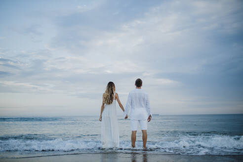 Couple holding hand while admiring view standing at water's edge on beach - GMLF00688