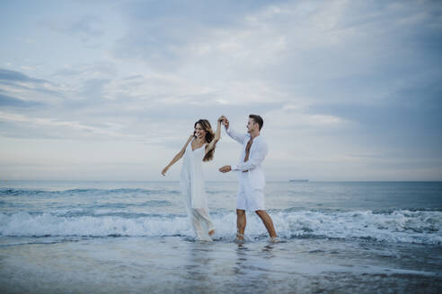 Young couple spinning woman while dancing in water at beach - GMLF00691