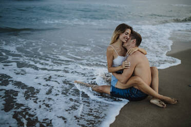 Couple embracing each other while sitting at water's edge on beach - GMLF00697
