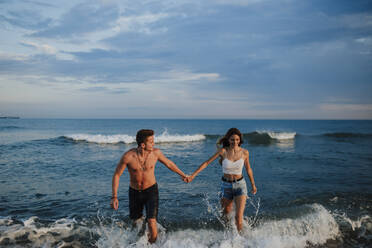 Couple holding hand while walking in water at beach - GMLF00700