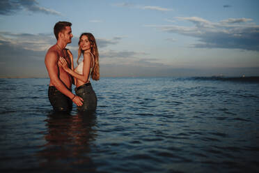 Man and woman standing in water during sunset - GMLF00703