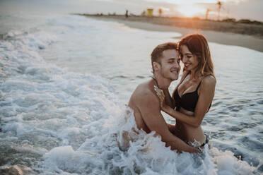 Smiling couple enjoying while sitting in water at beach - GMLF00715